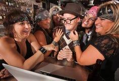 Biker Women Flirting with Computer Geek. Motorcycle gang members flirting with happy nerd on laptop royalty free stock photos