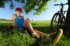 Biker. Young lady relaxing after cycling on a green lush meadow Stock Photography