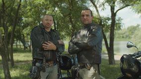 Bikers with arms crossed posing near motorbike stock footage