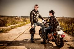 Bikers couple Man and woman near a motorcycle on the road stock photos