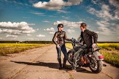 Bikers couple Man and woman near a motorcycle on the road royalty free stock photo