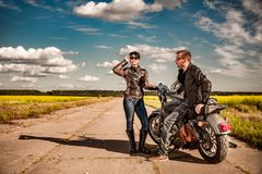 Bikers couple Man and woman near a motorcycle on the road royalty free stock images