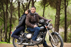 Bikers couple resting. In the forest, two models posing on the motorcycle, active lifestyle, fashion style, romance and extreme concept Royalty Free Stock Images