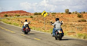 Bikers on Highway. Bikers Riding Down the Arizona Highway in Summer Day. Biking Photo Theme. Transportation Collection Stock Photography