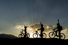 Bikers on hilltop at sunset. Silhouettes of bikers with raised hands on hilltop at sunset Royalty Free Stock Photos