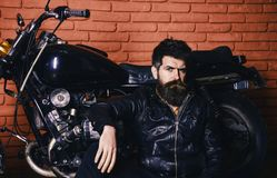 Bikers lifestyle concept. Man with beard, biker in leather jacket near motor bike in garage, brick wall background. Hipster, brutal biker on pensive face in stock photography