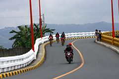 Bikers and motorcycle riders cross the Tumana Bridge in Marikina City. MARIKINA CITY, PHILIPPINES - JULY 30, 2017: Bikers and motorcycle riders cross the Tumana Stock Image
