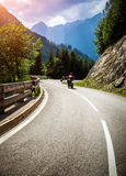 Bikers on mountainous race. Curve road in Alpine mountains, Austria, Europe, extreme touring, happy lifestyle, travel and journey concept Royalty Free Stock Photo