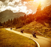 Bikers on mountains road in sunset. Group of motorcyclists riding on curves mountainous road, race of motorbike in Alps, beautiful pine forest, red sunset light Royalty Free Stock Photos