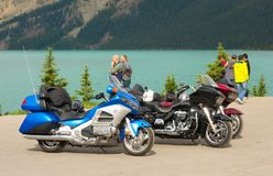 Bikers pausing to admire the view of a turquoise-colored lake in northern canada. A group of men touring the ice parkway on motor-bikes stopping for a rest and Royalty Free Stock Photos