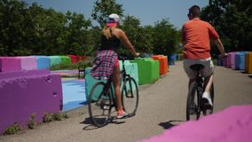 Bikers in Pittsburgh Pedal on Trail Near Colorful Blocks. Two bicyclists pedal away from camera on a trail in Pittsburgh`s South Side past colorful safety stock footage