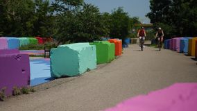 Bikers in Pittsburgh Travel on Trail Near Colorful Blocks. Two bicyclists pedal towards camera on a trail in Pittsburgh`s South Side past colorful safety stock video