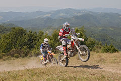 Bikers riding enduro motorcycles KTM 510 and KTM EXC 250. In the green mountains during the Italian championship Motorally Terre di Romagna, on July 5, 2015 in Stock Photo