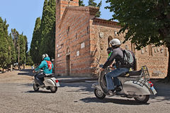 Bikers riding vintage scooters Vespa. Bikers riding vintage italian scooters Vespa passing in front of the medieval church during the scooter rally Raduno Stock Image