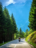 Bikers on the road in Alps. European tour, active lifestyle, driving motorcycle, enjoying freedom, summer holidays, traveling and tourism concept Royalty Free Stock Image