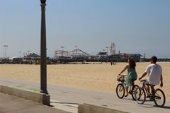 Bikers and Santa Monica Pier. Just walking at Santa Monica and took a perfect picture of a couple cycling in front of the Santa Monica Pier royalty free stock image