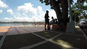 Bikers standing by huge tree. silhouettes. San Pablo City, Laguna, Philippines - September 8, 2015: Cyclists standing by under the tree at the side of the lake stock footage