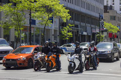 Bikers at stop light in city. Bikers chatting at a stop light in downtown Montreal Stock Images