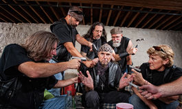 Bikers Threaten Sitting Man Royalty Free Stock Photos