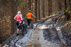 Bikers travel in difficult conditions in autumn forest.  Royalty Free Stock Photo