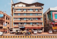 Bikers and vehicles moving past colorful modern buildings on indian street Stock Photo