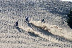 Bikes. Three bikes racing up a sand dune Royalty Free Stock Image