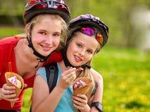 Bikes as meninas que dão um ciclo comendo o cone de gelado no parque Imagem de Stock Royalty Free