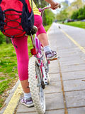 Bikes bicyclist girl. Children feet and bicycle wheel. Low section. Royalty Free Stock Image