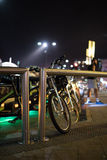 Bikes in a bike rack set in a nighttime cityscape Stock Photo