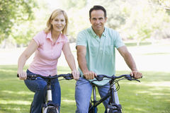 bikes couple outdoors smiling Στοκ εικόνα με δικαίωμα ελεύθερης χρήσης