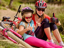 Bikes cycling family. Mother and daughter sitting road near bicycles. Royalty Free Stock Image
