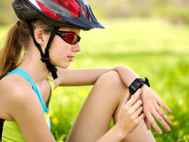 Bikes cycling girl. Bicyclist girl watch on smart watch. Stock Photography