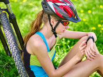 Bikes cycling girl. Bicyclist looks on smart watch. Royalty Free Stock Images