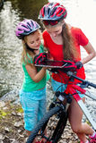 Bikes cycling girl. Children rides bicycle. Bicyclist watch tablet computer. Royalty Free Stock Image