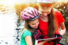 Bikes cycling girl. Children rides bicycle. Bicyclist watch tablet computer. Stock Photo