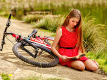 Bikes cycling girl has a rest and read book into park. Royalty Free Stock Images