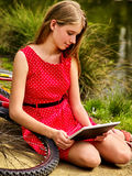 Bikes cycling girl into park. Children watch tablet pc. Stock Images