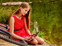 Bikes cycling girl into park. Children watch tablet pc. Royalty Free Stock Photo