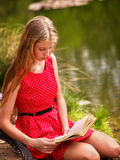 Bikes cycling girl into park. Girl read book leaning on  bicycle on shore. Royalty Free Stock Photography