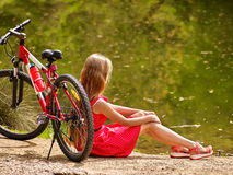 Bikes cycling girl into park. Girl sits leaning on  bicycle on shore. Royalty Free Stock Photos