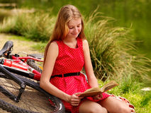 Bikes cycling girl into park read book bicycle on shore. Stock Photos