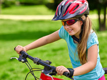Bikes cycling girl rides bicycle on green grass in park outdoor. Royalty Free Stock Photography