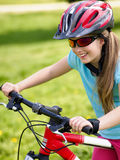 Bikes cycling girl rides bicycle on green grass in park outdoor. Stock Photo