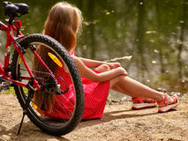 Bikes cycling girl sits on bicycle shore into park . Royalty Free Stock Photography