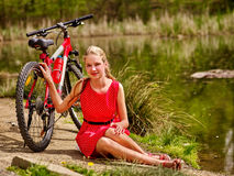 Bikes cycling girl sits near bicycle on shore into park. Royalty Free Stock Photo