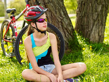 Bikes cycling girl wearing helmet have a rest sitting under tree. Stock Photos