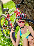 Bikes cycling girl wearing helmet have rest sitting under tree. Stock Photography