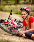 Bikes cycling girl wearing helmet. Kid fell off bike. Royalty Free Stock Photography