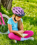 Bikes cycling girl wearing helmet read book rest near bicycle. . Royalty Free Stock Photos