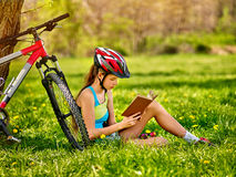 Bikes cycling girl wearing helmet read book rest near bicycle. Stock Images